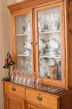 Dinner service displayed in a wooden dresser with an Art Nouveau style lamp and old leather bound books