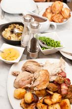 Family dinner laid out on a dining table with a platter of carved roast meat, roast potatoes, peas, vegetables and gravy for a wholesome meal