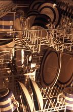 Detail of the interior of a dishwasher showing a range of clean crockery and cutlery
