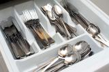 Open cutlery drawer with inside dividers filled with silver stainless steel knives, forks, spoons and teaspoons for eating