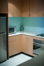 Interior of a modern kitchen with wooden cabinetry, a microwave, metallic refrigerator, undercounter oven and hob