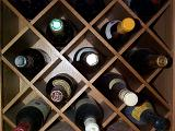 Wooden wine rack with individual partitions filled with bottles of a variety of different vintages and varieties of wine