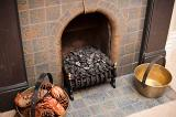 Fireplace with coal or anthracite in the old-fashioned metal grate in the hearth and old brass cauldrons with wood and cones on either side