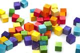 Bright multicolored wooden toy blocks in the colors of the rainbow scattered in a heap on a white background