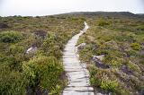 Long path uphill with wooden walkway made of old withered logs or planks, through rough rocky hill terrain covered with grass