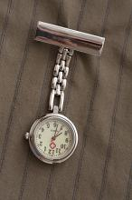 Nurses silver metal fob watch on a chain with a clip for fastening it to her uniform