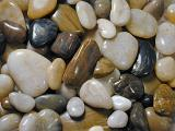 Background texture of smooth water worn pebbles from a beach or riverbed in different shapes and sizes
