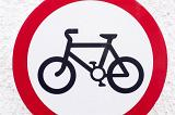 No Bicycles forbidding road sign with black image of a bicycle on white background inside the red circle, viewed cropped in close-up
