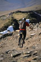 a unicyclist negotiating the side of a mountain