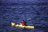 a man paddling through the water on a yellow ocean kayak