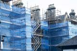 Scaffolding and protective sheeting on a building site covering a large building during repairs and maintenance