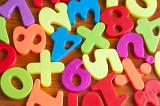 Close up showing fridge magnets of numbers and mathematical symbols, in bright colours over wood effect background