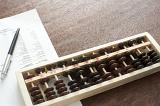 Wooden abacus being used for accounting lying on a desk with a balance sheet and ballpoint pen viewed from above