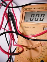 Close Up of Multimeter Electronic Measuring Instrument with Reading of Zero, Black and Red Test Lead Wires on White Background